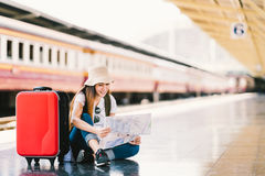 使用普通地方地图的亚裔背包旅客妇女,单独选址在有行李的火车站平台 免版税库存图片