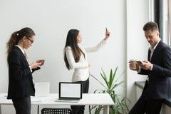 使用智能手机发短信的买卖人,采取selfie在offic 免版税库存照片