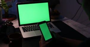 使用智能手机和一台便携式计算机的手有绿色屏幕的 移动式摄影车移动从右到左 股票录像