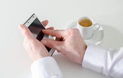 使用智能手机和喝咖啡的商人 免版税库存图片