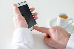 使用智能手机和喝咖啡的商人 免版税库存照片