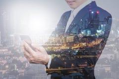 使用智能手机和夜城市视图的商人 库存照片
