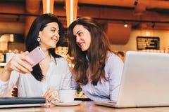 使用智能手机和微笑,两名年轻愉快的妇女在咖啡馆坐在膝上型计算机前面的桌上, 库存图片