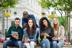 使用智能手机和片剂计算机的不同种族的青年人 免版税库存图片