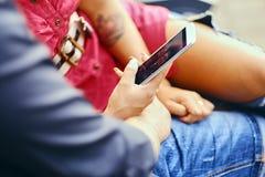使用智能手机和瞬时笔谈的一对夫妇 免版税库存照片