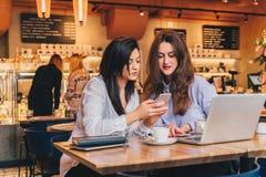 使用智能手机和笑,两名年轻愉快的妇女在咖啡馆坐在膝上型计算机前面的桌上, 库存照片