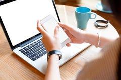 使用智能手机和膝上型计算机的一个少妇在咖啡馆 免版税库存照片