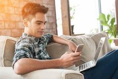 使用智能手机和膝上型计算机的商人在沙发 免版税库存图片