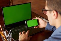 使用智能手机和膝上型计算机的商人输入办公室的后面观点的 绿色屏幕大模型 自由职业者工作区 人们 库存图片