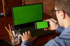 使用智能手机和膝上型计算机的商人输入办公室的后面观点的 绿色屏幕大模型 自由职业者工作区 人们 免版税库存照片