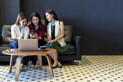 使用智能手机和膝上型计算机的小组迷人的美丽的亚裔妇女,聊天在沙发在咖啡馆,现代生活方式 免版税库存照片