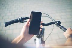 使用智能手机和自行车的女孩为旅行  库存图片