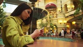 使用智能手机在喷泉附近在购物中心,购物中心的女商人 放松和宁静 股票录像