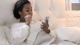 使用智能手机在床上时,庆祝成功的年轻非洲妇女,当 股票录像