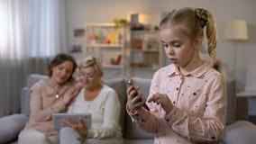 使用智能手机应用程序、祖母和母亲卷动片剂的微笑的孩子 股票录像