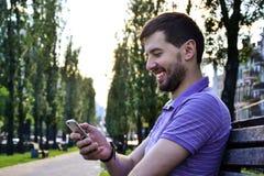 使用智能手机微笑的快乐的人 免版税库存图片