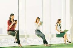 使用智能手机数字式片剂和便携式计算机的三个亚裔女孩在现代办公室在日落 信息技术生活方式 免版税库存照片