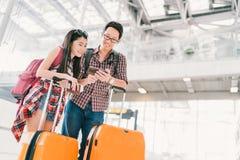 使用智能手机检验飞行或网上报到的亚裔夫妇旅客在机场,有护照和行李的 免版税库存图片