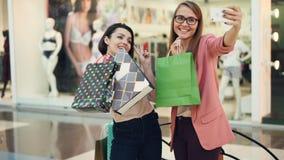 使用智能手机照相机保存设备和摆在,愉快的shopaholics采取与纸袋的selfie在购物中心 股票视频