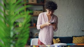 使用智能手机照相机,有天赋的女性设计师拍摄纸拼贴画的照片在笔记本的 平的位置,装饰 影视素材