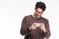 使用智能手机的一个微笑的人的画象 免版税图库摄影
