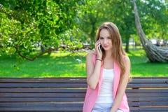 使用智能手机的一名可爱的年轻职业妇女的画象,当坐一个长木凳在公园,微笑时 库存照片