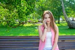 使用智能手机的一名可爱的年轻职业妇女的画象,当坐一个长木凳在公园,微笑时 图库摄影