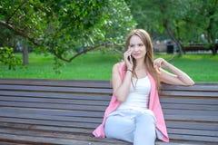 使用智能手机的一名可爱的年轻职业妇女的画象,当坐一个长木凳在公园,微笑时 免版税库存图片