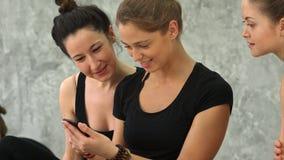 使用智能手机的三个少妇和笑在锻炼以后在瑜伽类 库存照片