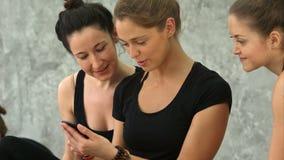 使用智能手机的三个少妇和笑在锻炼以后在瑜伽类 股票视频