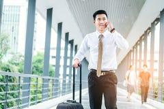 使用智能手机的专业商人旅行谈话在他的 图库摄影
