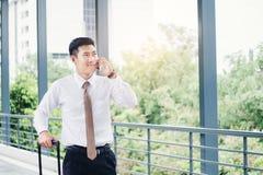 使用智能手机的专业商人旅行谈话在他的 库存照片