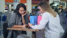 使用智能手机的两名妇女在咖啡馆在商城 免版税库存图片