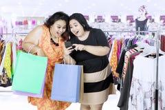 使用智能手机的两名妇女在购物中心 库存照片