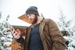 使用智能手机的严肃的人站立户外在冬天 免版税库存照片