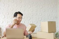 使用智能手机的亚裔中年人有工作的膝上型计算机的在h 免版税库存照片