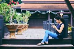 使用智能手机的亚裔女孩 免版税库存照片