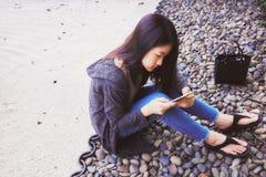 使用智能手机的亚裔女孩 免版税库存图片