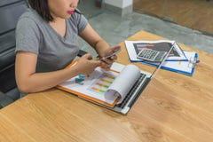 使用智能手机的亚裔妇女与商务伙伴联系 免版税库存照片