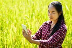 使用智能手机的亚裔妇女农夫 免版税库存照片