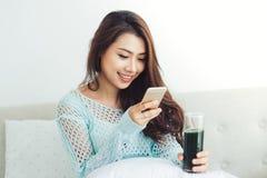 使用智能手机的亚裔妇女坐长沙发 免版税库存图片
