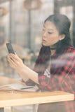 使用智能手机的亚裔学生和坐在咖啡馆 免版税库存照片