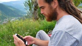 使用智能手机的享受发短信的年轻人画象传送分享通信微笑的网上sms信息愉快 股票视频