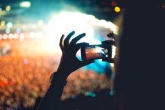 使用智能手机的人剪影采取录影在音乐会 与采取图片和录影的行家的现代生活方式 库存照片