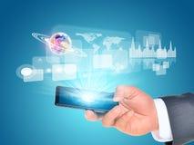 使用智能手机的人手 在电话附近的地球 免版税库存图片