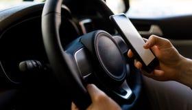 使用智能手机的人特写镜头,当驾驶的测试在汽车时 库存照片