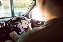 使用智能手机的人的中央部位在汽车 免版税库存照片