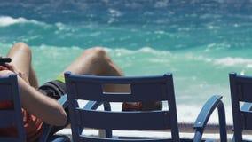 使用智能手机的人说谎在海海滩,放松与小配件,后面看法 股票视频