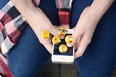 使用智能手机的人送emojis 免版税库存照片