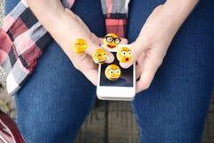 使用智能手机的人送emojis 免版税库存图片